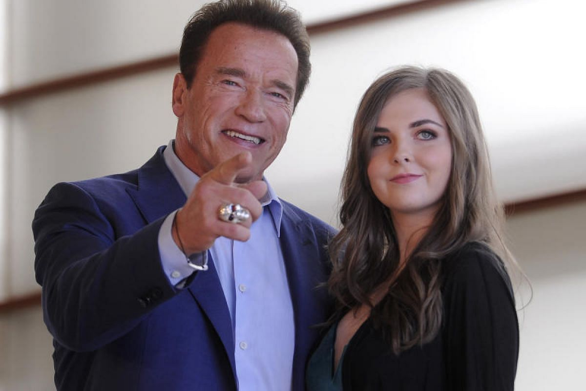 Producer and former governor of California Arnold Schwarzenegger and US singer Maisy Kay pose during a photocall to promote the film Wonders Of The Sea 3D.