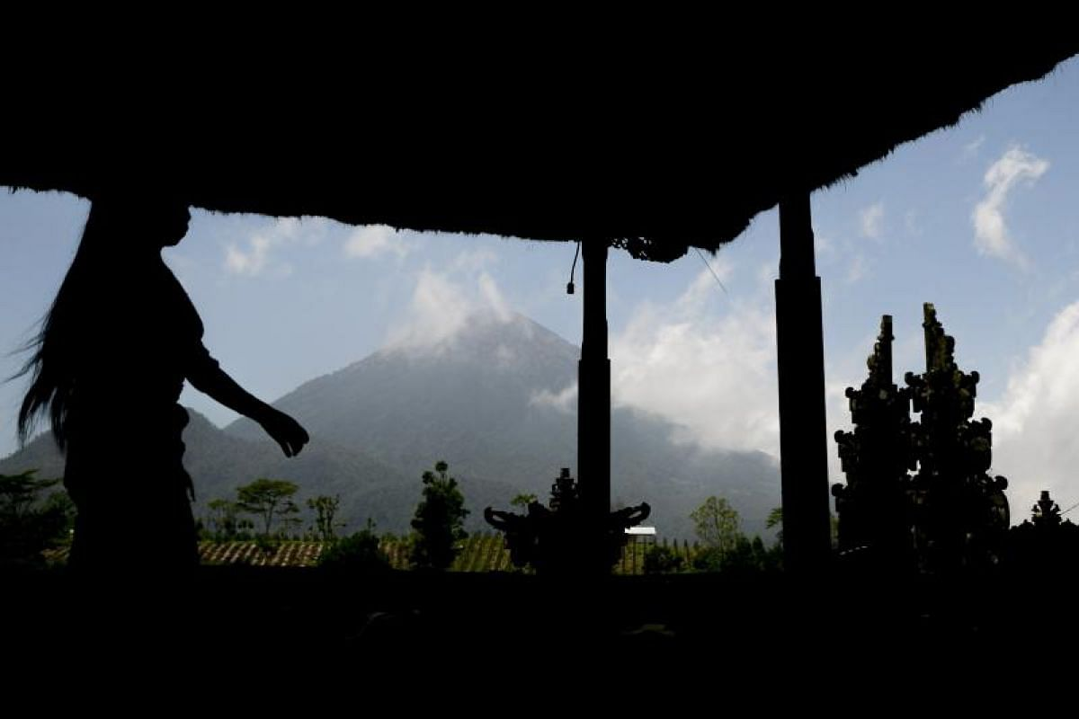 A villager holds a prayer for Mount Agung at a Hindu temple in Pemuteran village on Sept 27.