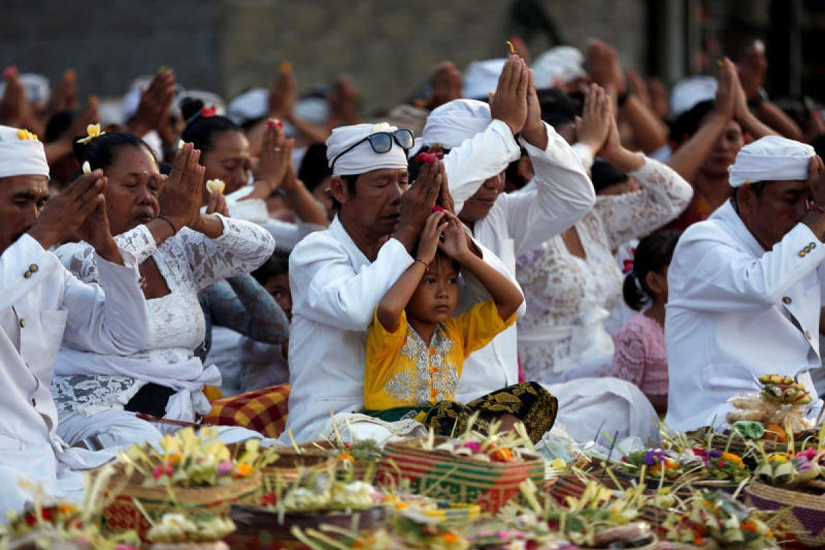 Local people pray for safety on the beach near Mount Agung on Sept 27.