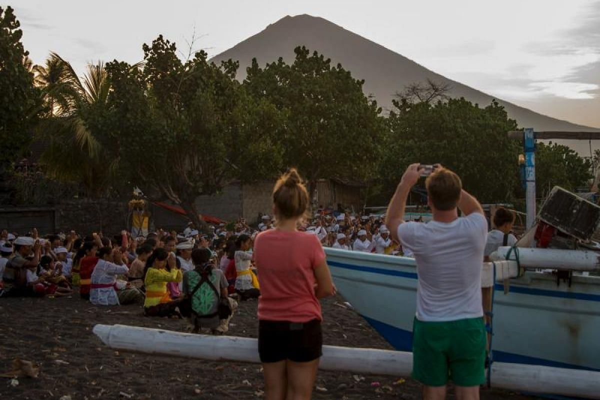 Tourists take pictures of a prayer session on Amed beach as Mount Agung is seen in the background on Sept 27. Indonesian authorities are on standby to divert flights destined for the holiday island.