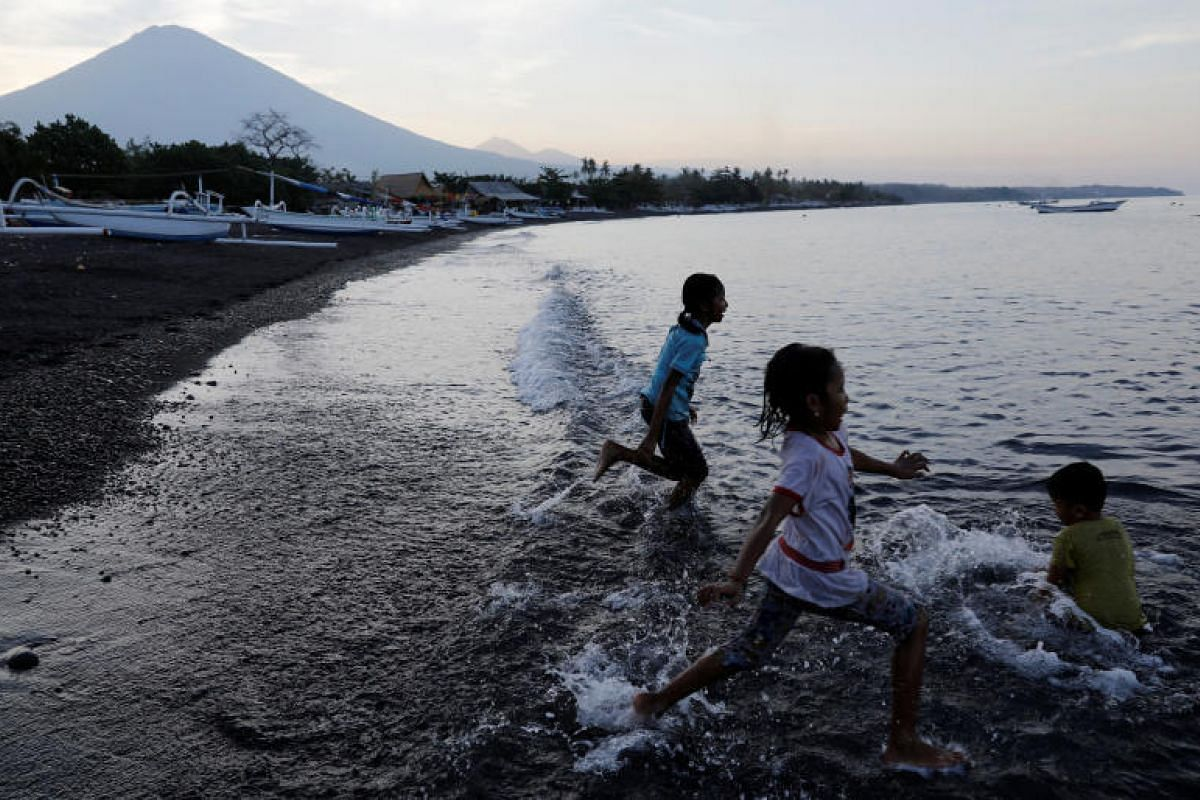 Balinese children continue enjoying themselves on the beach outside the danger zone near Mount Agung.