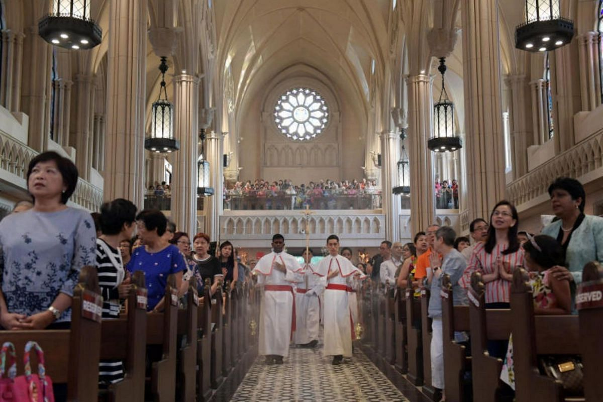 Altar server swing thuribles with incense as they lead the entrance procession into the church.