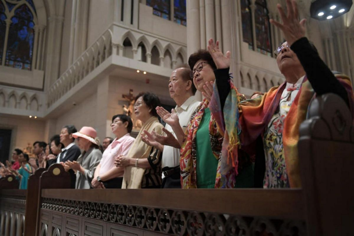 Attendees participate in the first mass held at the Novena Church.