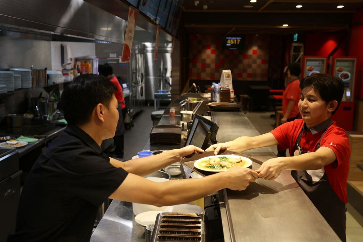Mr Tay Teck Leong (right), who works at food and beverage chain Han's Group and has a hearing disability, takes on duties such as serving food.