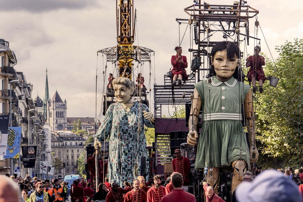 Two giants puppets are paraded down a street in Geneva, Switzerland, October 1, 2017. PHOTO: EPA-EFE