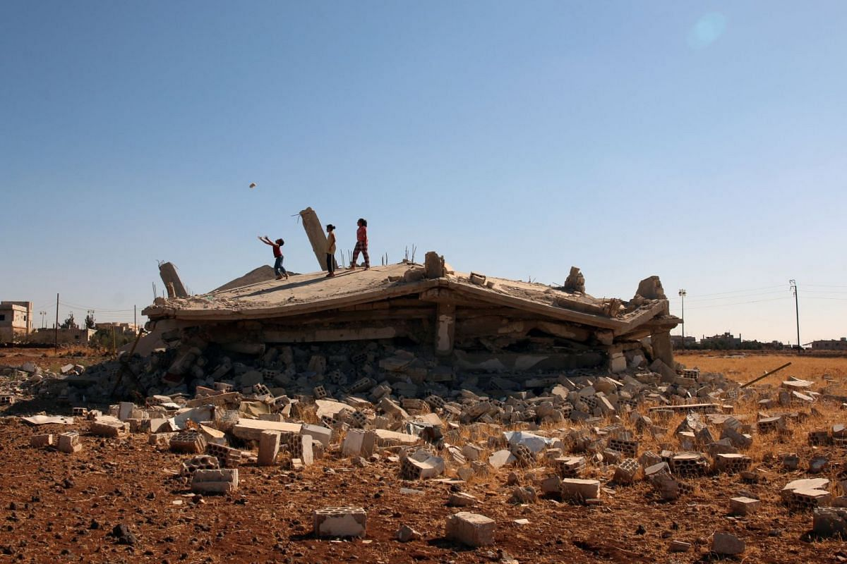 Syrian children play on a damaged house in Bosra al Sham town, Syria, October 1, 2017. PHOTO: REUTERS