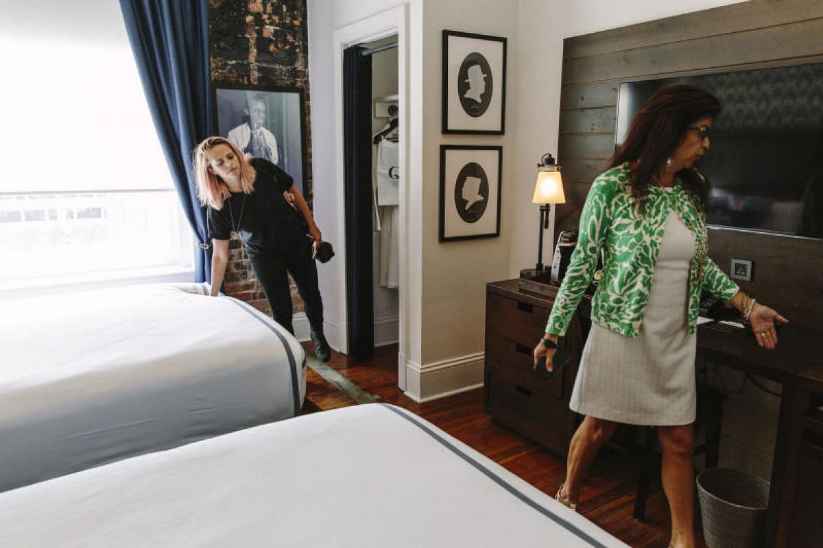 Hotel reviewer Cameron Todd checks a mattress in a hotel room at New Orleans' Queen and Crescent Hotel during a tour led by account director Ingrid Palomo-D'Aquin.