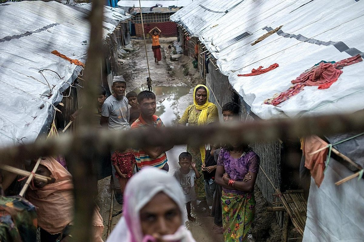 Ms Roshida Begum (standing at the top), a Rohingya who fled Myanmar some 25 years ago at the age of 11, outside the shack in Bangladesh's Kutupalong refugee camp where she lives with her family, and which she also now shares with 13 other new arrival
