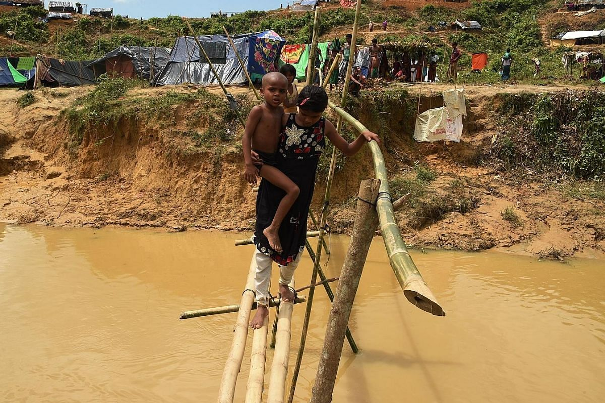 Young Rohingya refugees crossing a canal using a bamboo bridge at a newly expanded camp known as Kutupalong Extension.