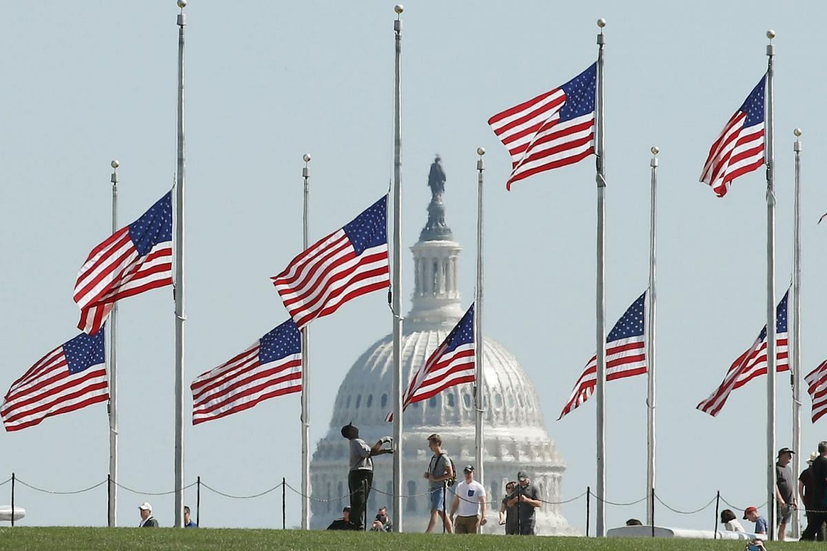 A Park Service employee lowers the US flags on the grounds of the Washington Monument to half-staff, in Washington, DC.