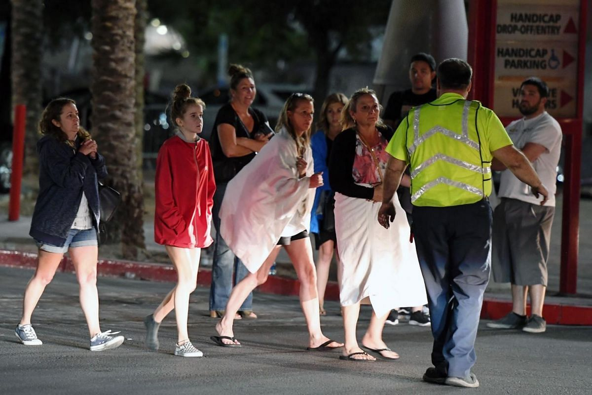People are directed to rides outside the Thomas & Mack Centre after a mass shooting at a country music festival in Las Vegas.