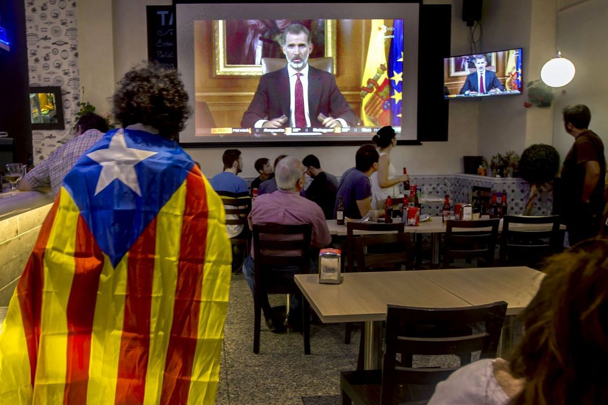 People in a bar listen to the speech of Spanish King Felipe VI, two days after the illegal Catalonian referendum, in Barcelona, Spain, Oct 3, 2017. In his address, King Felipe accused the Catalan authorities of attempting to break the unity of Spain.