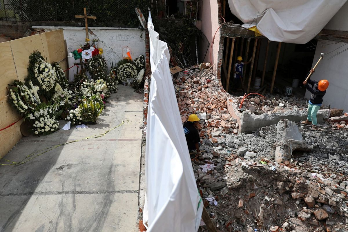 Wreaths and a Mexican flag are placed in tribute to the victims at the site of a building that collapsed in an earthquake in Mexico City, Mexico Oct 2, 2017. REUTERS