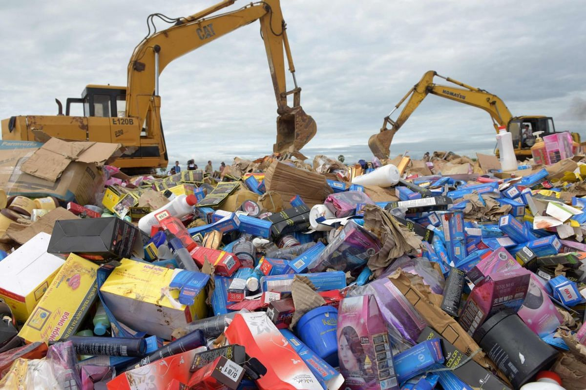 Excavators run over 60,000kg of counterfeit cosmetic products in Phnom Penh, Cambodia, October 3, 2017. PHOTO: AFP