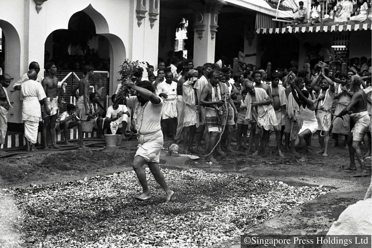 1978: A devotee walking barefoot across the 3m long pit of smouldering coal. The annual fire walking ceremony is held about a week before Deepavali.