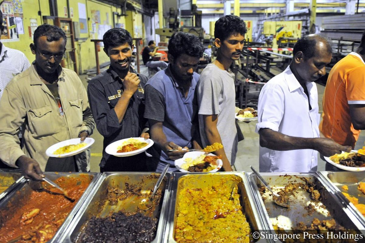 2010: Construction workers gathering in line to enjoy a buffet spread. The dinner is an annual tradition for the company, to help their workers to celebrate Deepavali.
