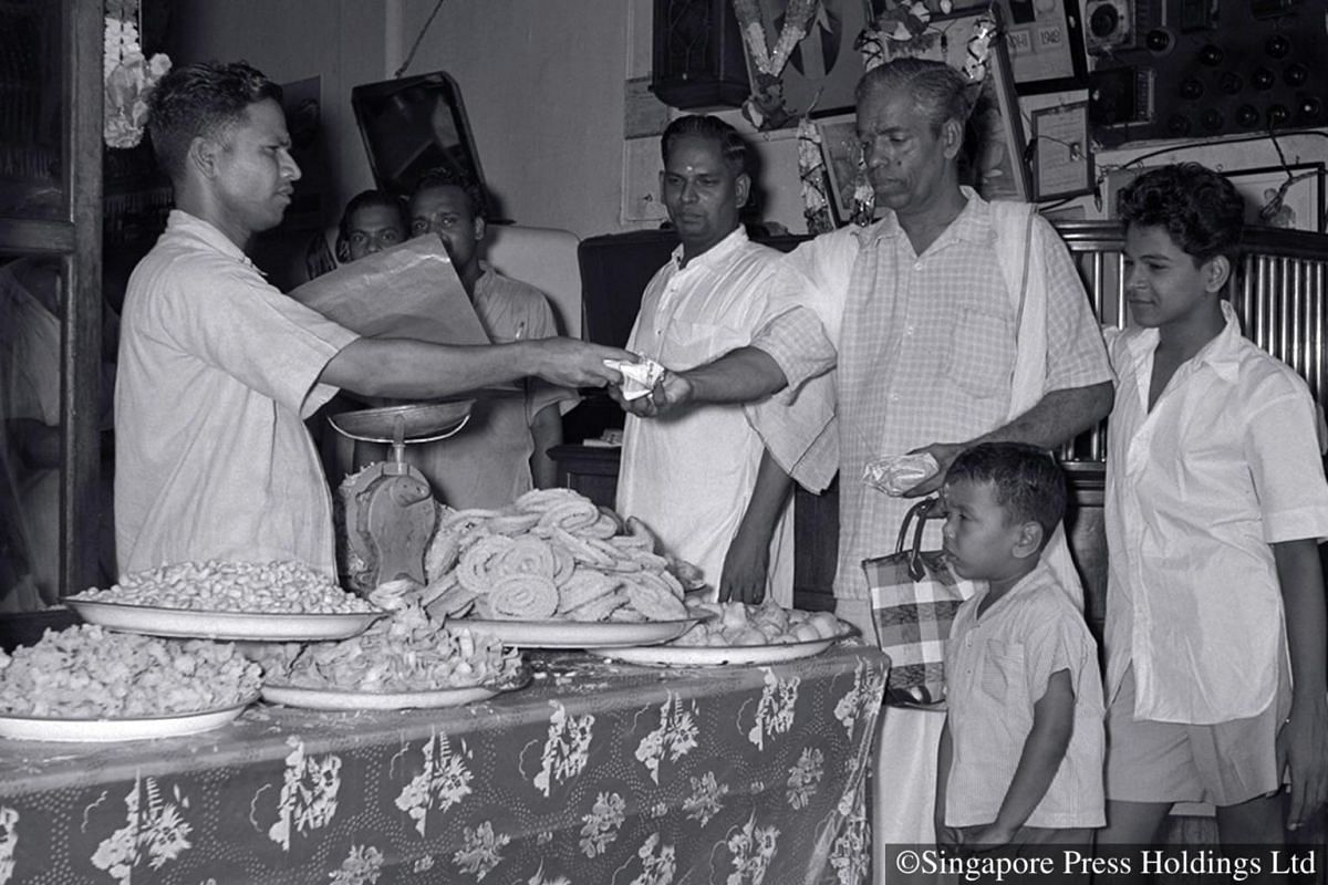 1956: Sweet and savoury snacks being purchased for Deepavali.