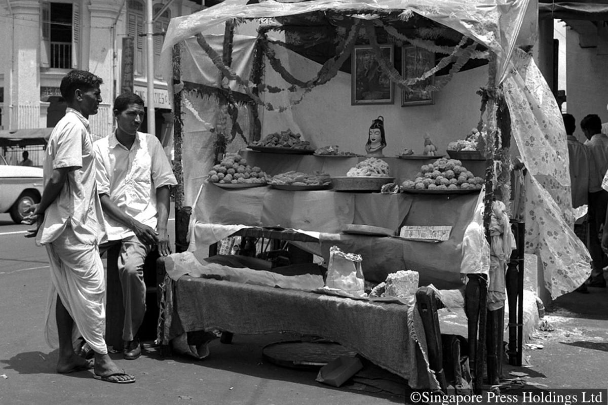 1960: A sweet vendor displaying his goods at a stall with decorations for Deepavali.