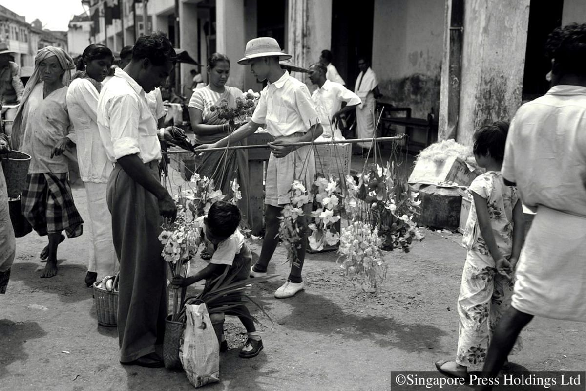 1952: A vendor selling flowers to Deepavali shoppers. Flowers play a symbolic role in Hinduism; they are offered to the deities as a sign of respect.