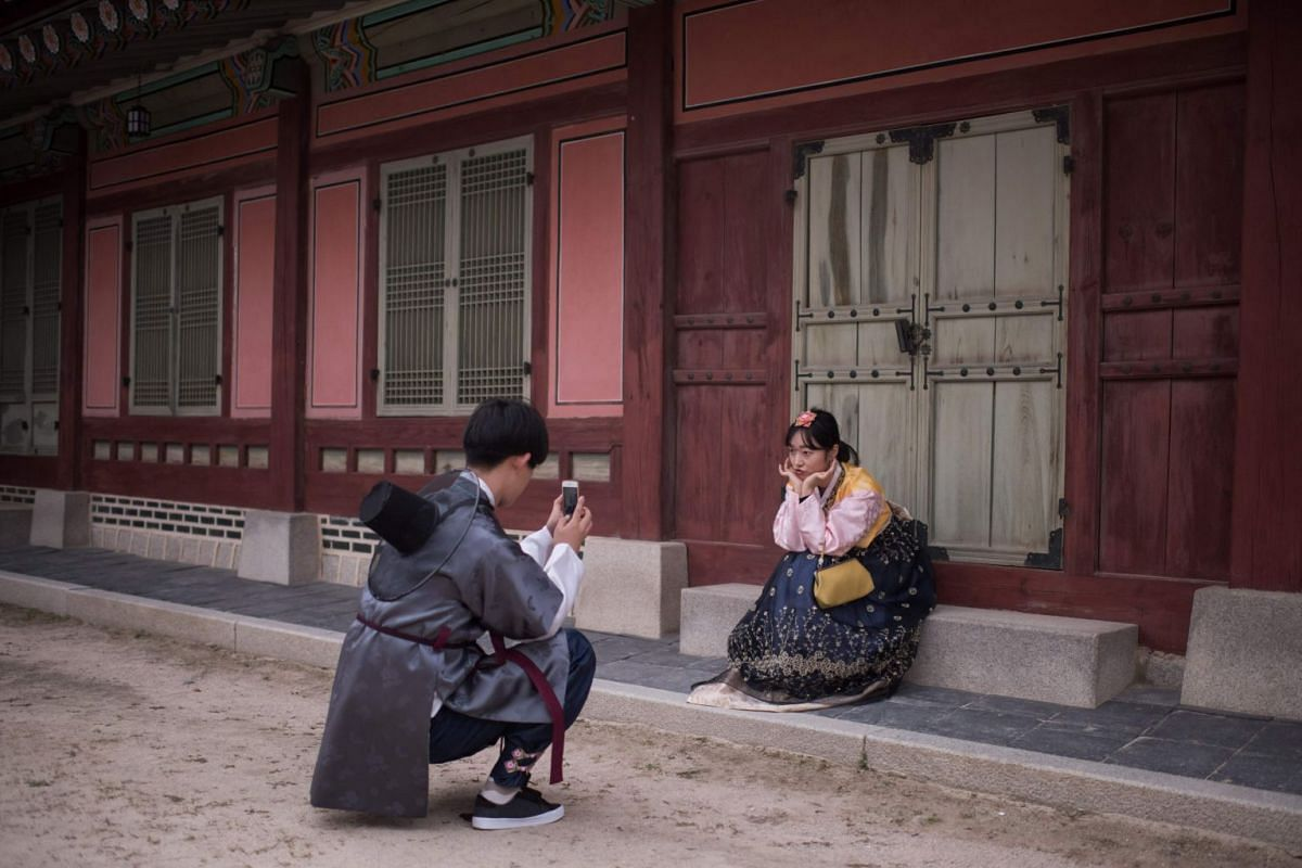 A woman wearing traditional Korean hanbok dress poses for photos at Gyeongbokgung palace in Seoul on Oct 3, 2017. PHOTO: AFP