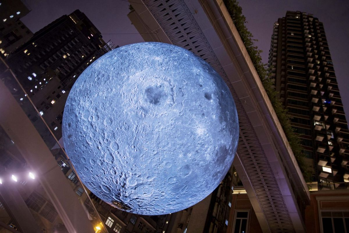 A 7-m-wide glowing sculpture of the moon by British artist Luke Jerram hangs in a shopping street in Hong Kong, China, Oct 4, 2017.  PHOTO: EPA-EFE