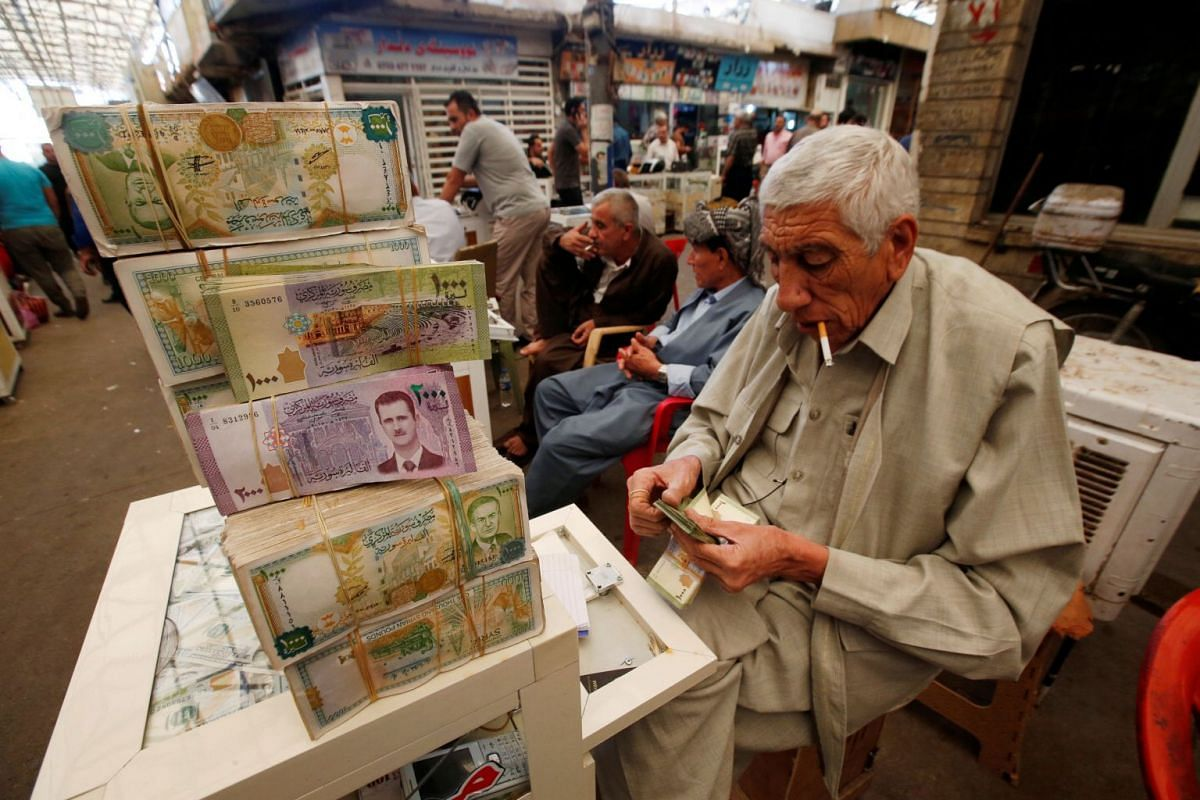 A man counts money at the stock exchange in Erbil, Iraq, Oct 4, 2017.  PHOTO: REUTERS