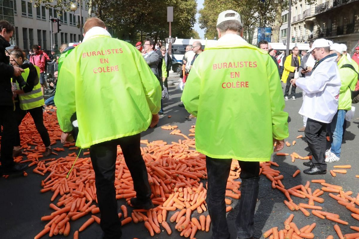 Tobacconists throw carrots on the street as they demonstrate against the increase in the price of cigarettes in Paris, France, Oct 4, 2017. PHOTO: AFP