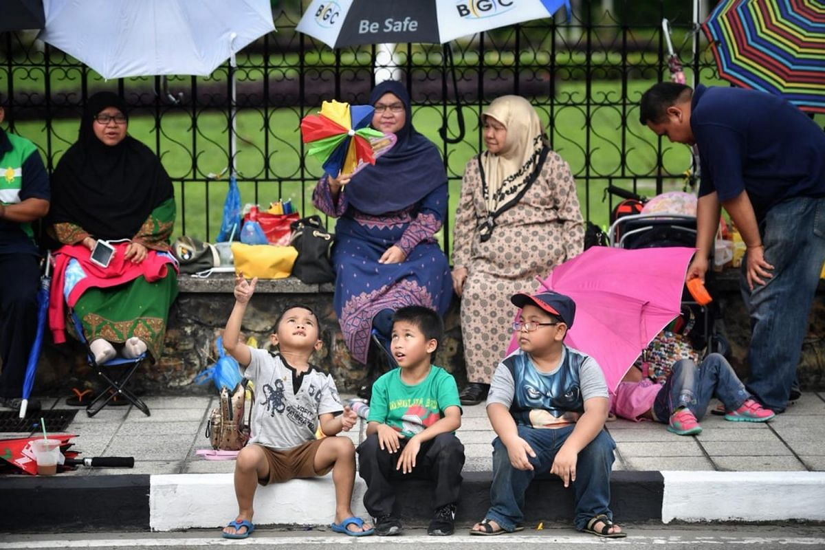 Bruneians sit along a roadside waiting for Brunei's Sultan Hassanal Bolkiah to ride past on a royal chariot during a procession to mark his Golden Jubilee.