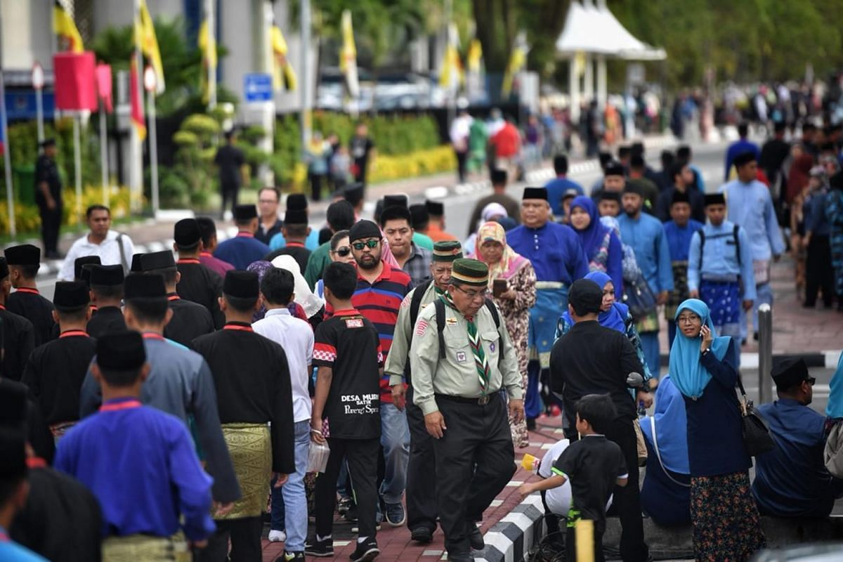 Crowds line the street before Brunei's Sultan Hassanal Bolkiah goes through the city during his Royal Procession.