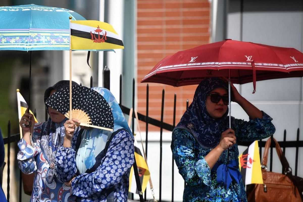 Women seek shelter from the heat as they wait for Brunei's Sultan Hassanal Bolkiah's Royal Procession.
