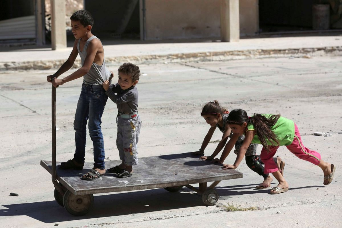 Children play along a street in the town of Tadef in Aleppo province, Syria, October 5, 2017. PHOTO: REUTERS