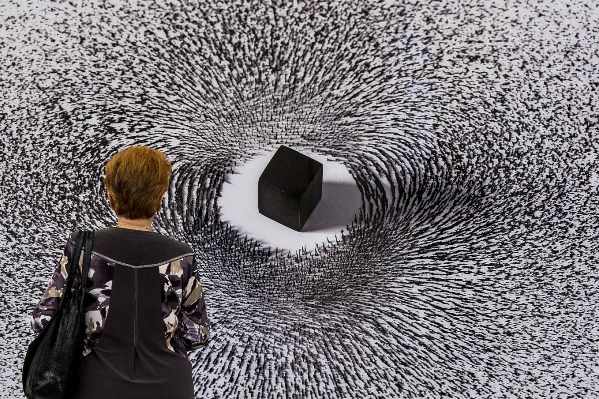 A woman looks at Saudi artist Ahmed Mater's Magnetism IV during an exhibition in Moscow, Russia, October 5, 2017. PHOTO: AFP