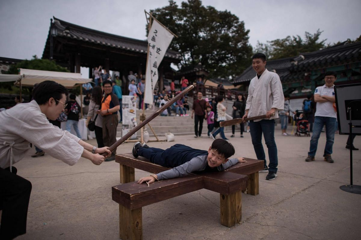 A boy takes part in a game featuring traditional methods of punishment, at the Namsan Hanok Village in Seoul, South Korea,  October 5, 2017.  PHOTO: AFP
