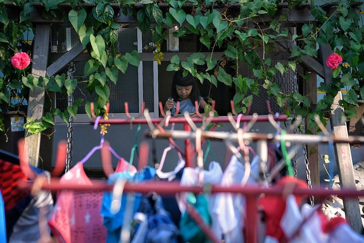 Lorong Buangkok resident Seah Hui Yun, nine, enjoys her breakfast. As the day starts, some residents busy themselves with chores, such as doing the laundry.