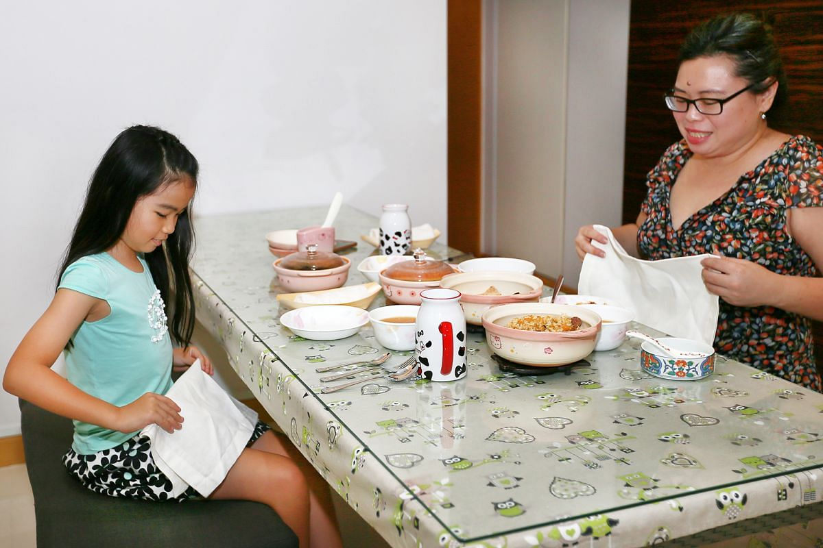 Ashley Ngeow and her mother, Ms Fion Phua, dining with a full table setting. Ms Phua enrolled her daughter in an etiquette class that taught her table manners for fine-dining.