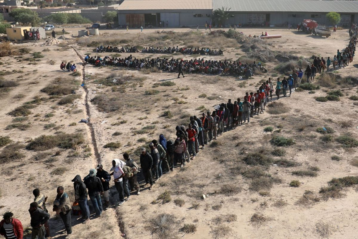 Migrants wait to be transported to a detention center, in Sabratha, Libya, on Oct 7, 2017. PHOTO: REUTERS