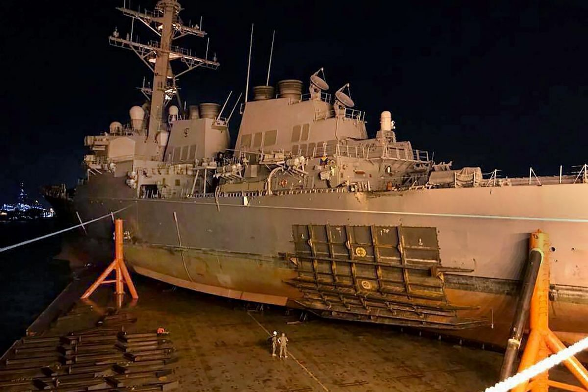 This handout photo from the US Navy, released on Oct 8, 2017 shows the guided missile destroyer USS John S. McCain being loaded onto heavy lift transport vessel MV Treasure. The USS John S. McCain collided with a tanker off the coast of Singapore on