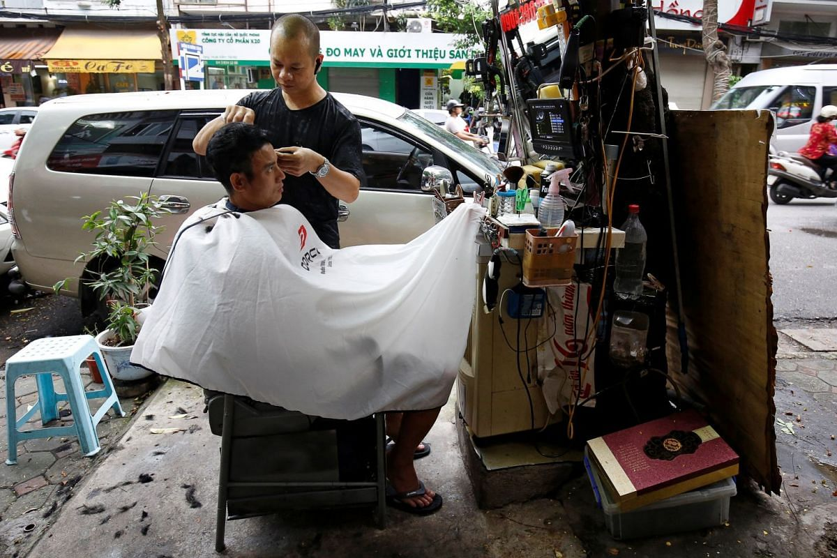 A man gets a haircut from a street barber  in Hanoi, Vietnam,  October 9, 2017. PHOTO: REUTERS