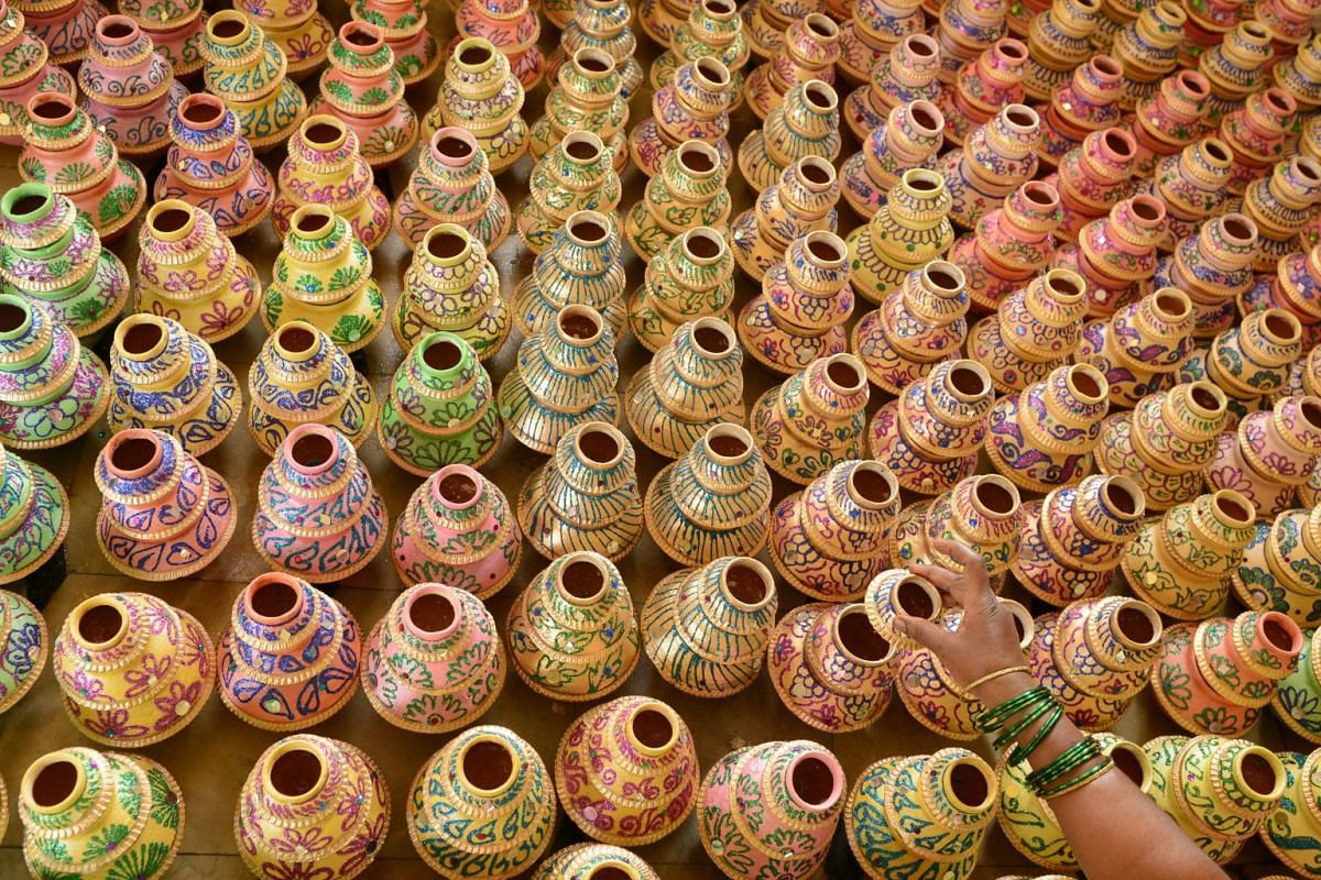 An artisit decorates earthenware oil pots in preparation for the Diwali festival in Hyderabad, India, Oct 9, 2017. PHOTO: AFP