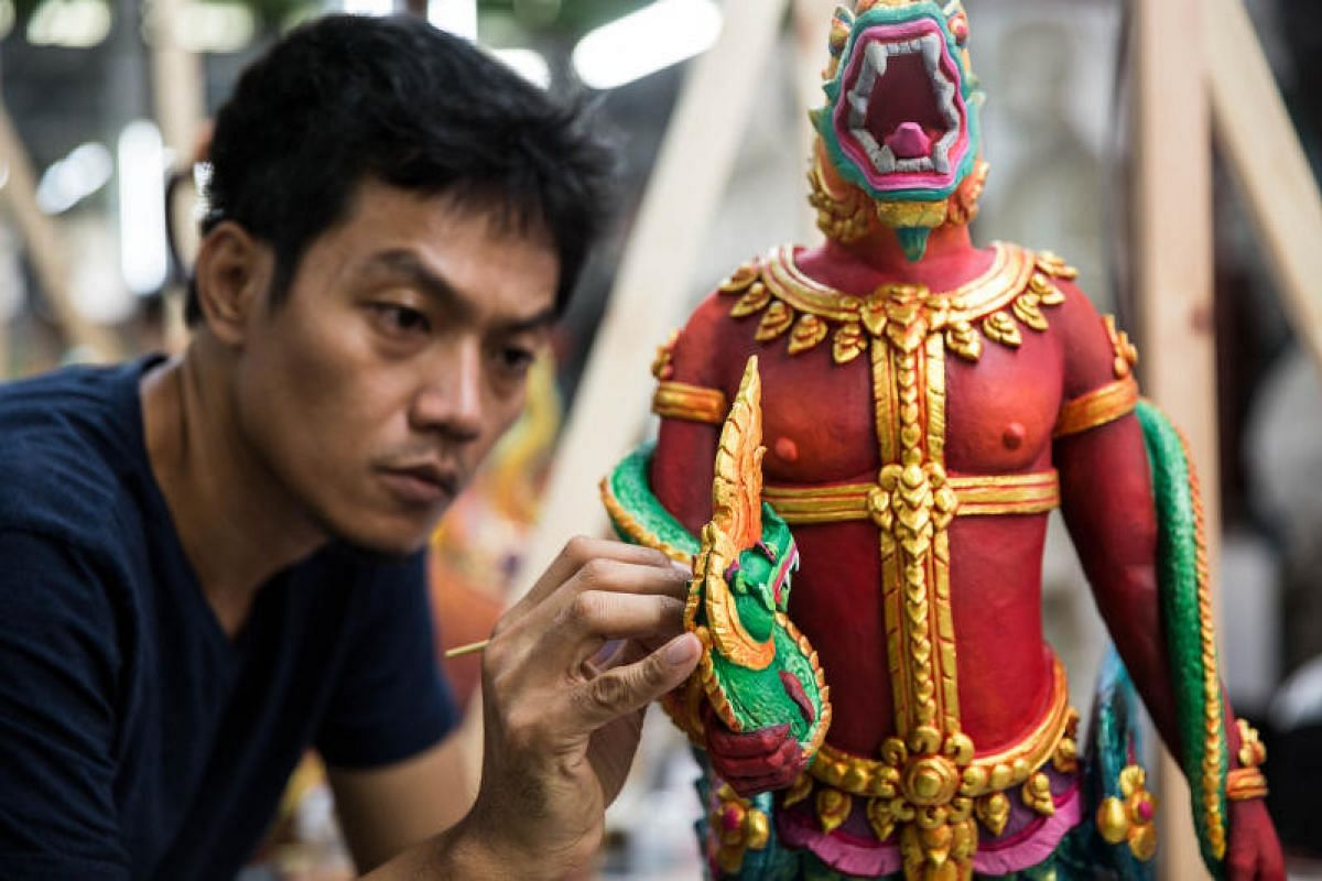 An artist painting a decorative item for the cremation ceremony of the King in a studio at the Fine Arts Department.