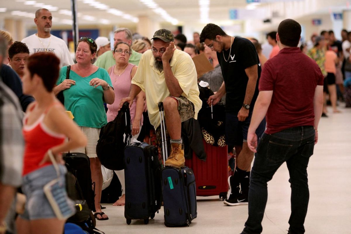 Stranded tourists and Puerto Ricans lining up at the airport as they try to leave after Hurricane Maria devastated power and communications across the island, in San Juan, Puerto Rico, on Sept 25, 2017.