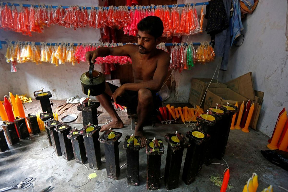 A worker pours liquid paraffin wax into small iron boxes to make candles ahead of the Hindu festival of Diwali, in Kolkata, India,  October 10, 2017. PHOTO: REUTERS