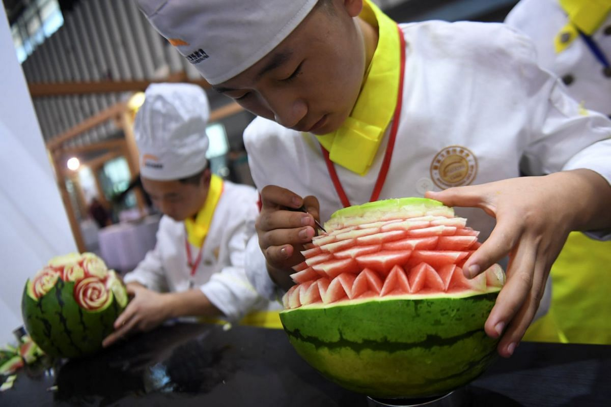 People carve watermelons during a competition in Nanjing, China October 9, 2017. PHOTO:  REUTERS
