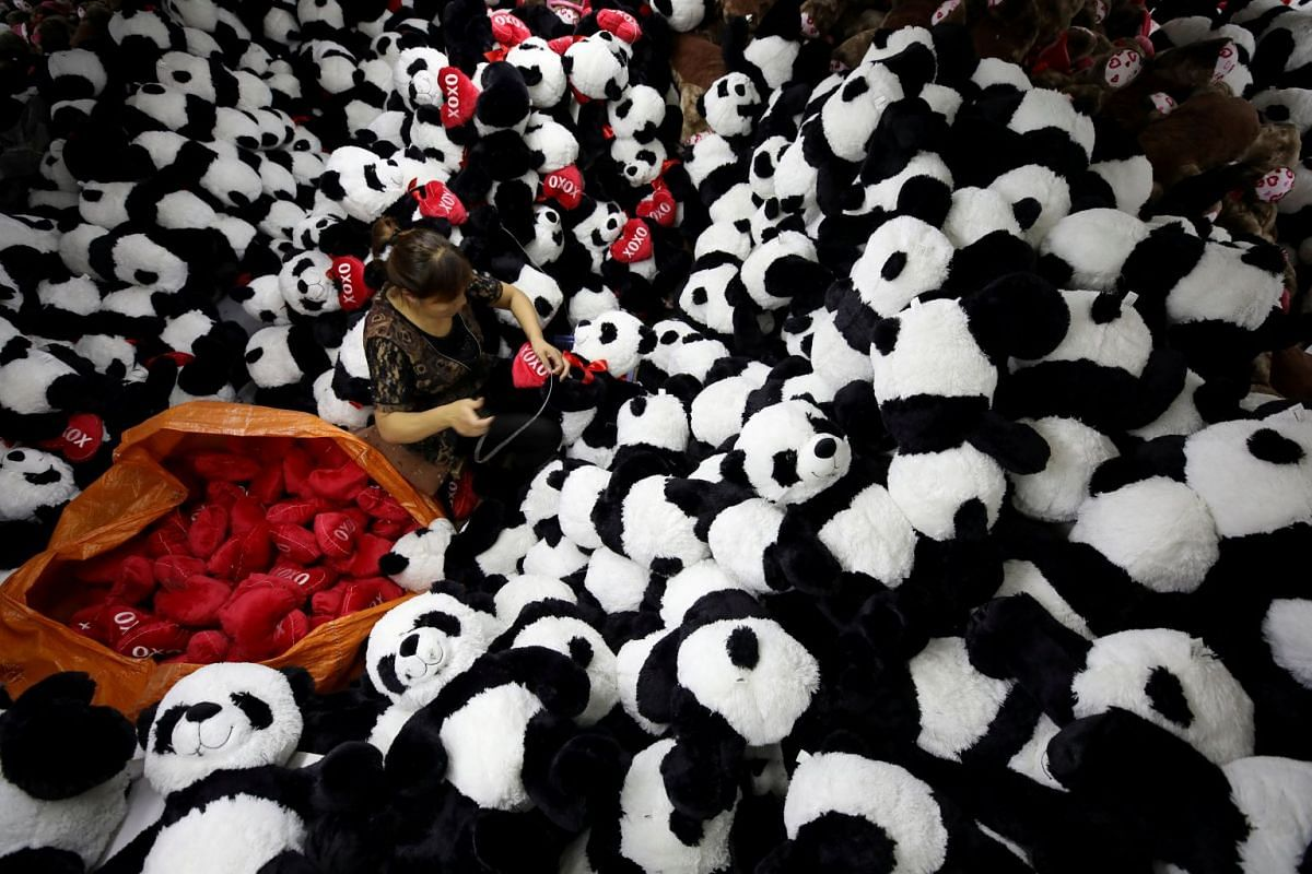 A worker processes panda soft toys for export at a factory in Jiangsu province, China, October 9, 2017. PHOTO: REUTERS