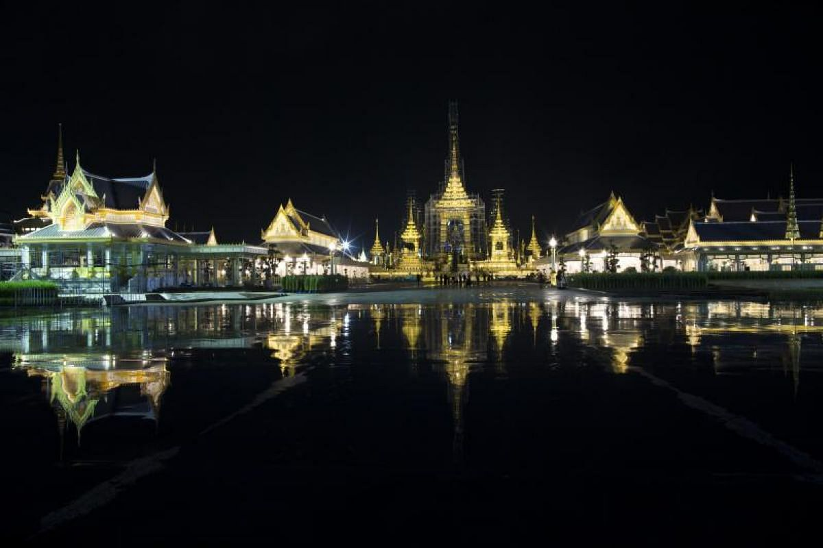 A general view of the royal crematorium is reflected in a puddle of water after heavy rain near the Grand Palace.