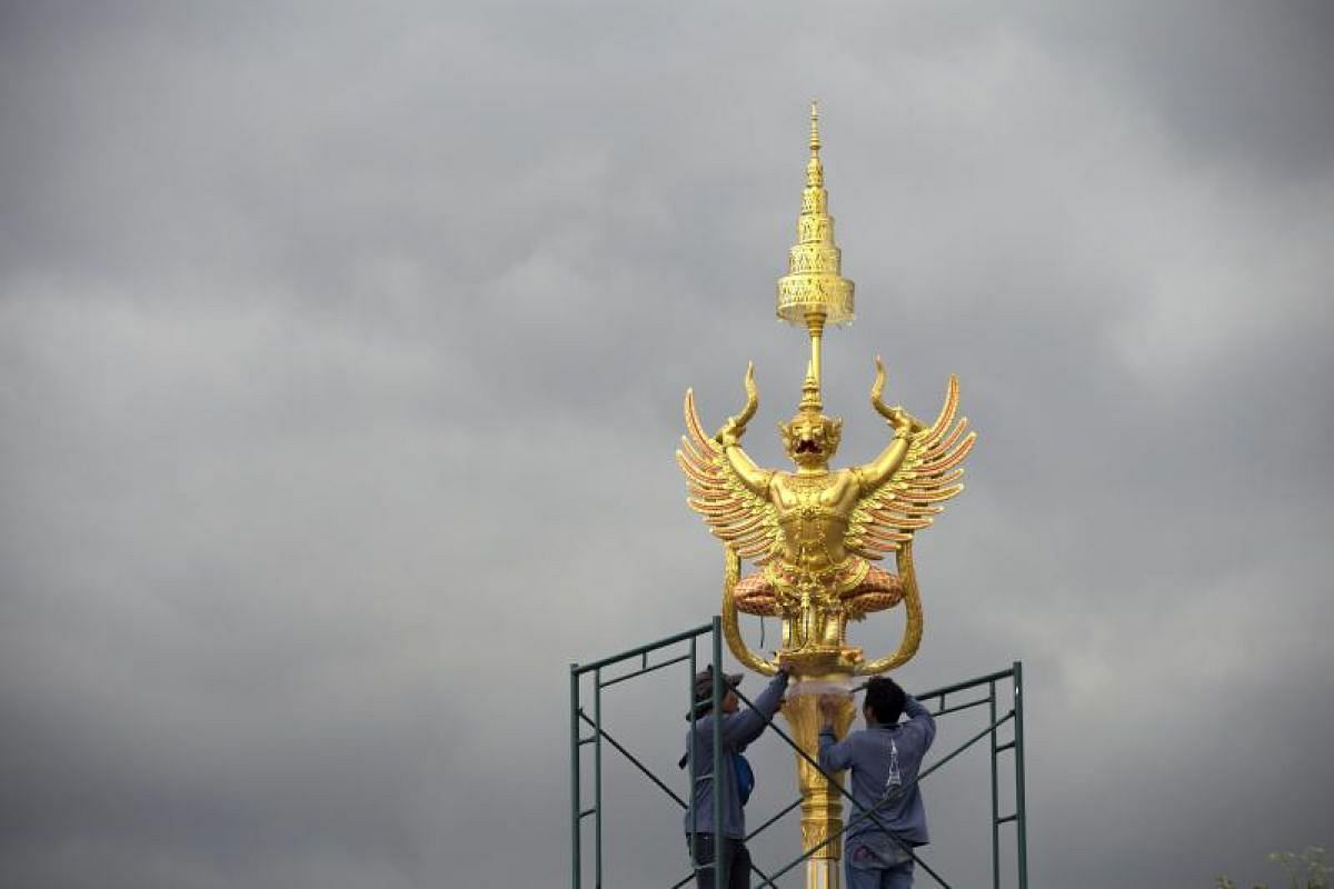 Thai workers install a sculpture of the legendary creature Garuda, found in both Hindu and Buddhist mythology, to adorn the elaborate complex of the royal crematorium.