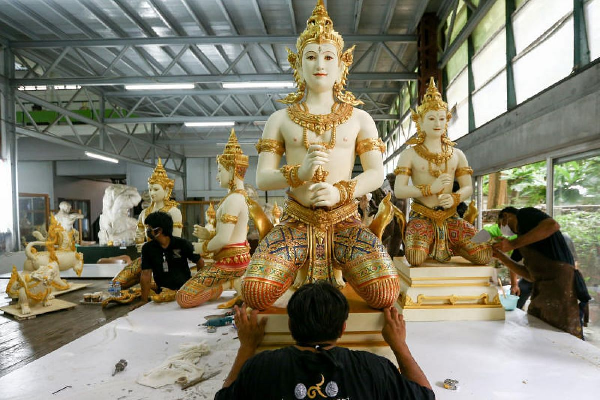 An artist works on a deity sculpture which will decorate the funeral pyre.