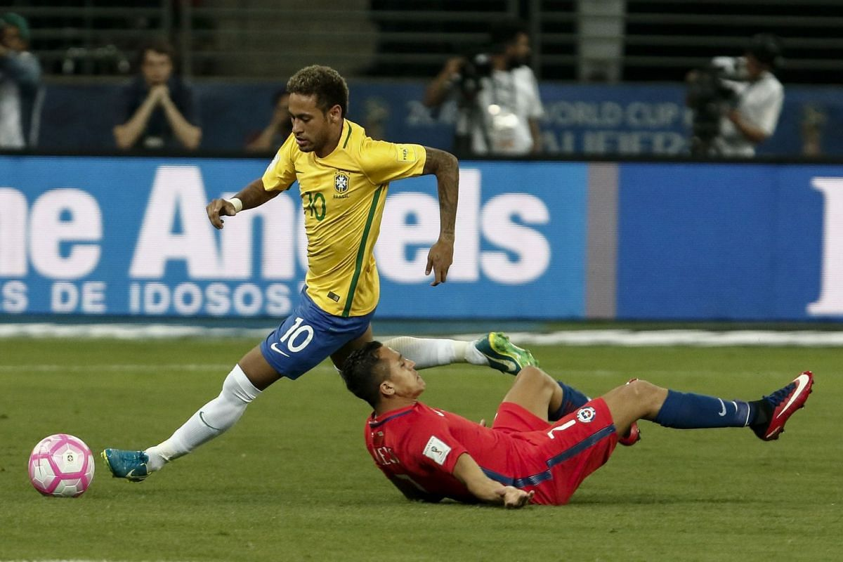 Brazil's Neymar (left) eludes Chile's Alexis Sanchez during their 2018 World Cup football qualifier match in Sao Paulo, Brazil, on October 10, 2017. Brazil beat Chile 3-0, dumping Chile out of the World Cup. Brazil went into the game with their place