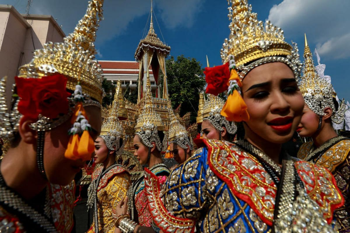 Traditional dancers standing next to the Great Victory royal chariot that will carry King Bhumibol's body in a giant ornate urn to the cremation site.