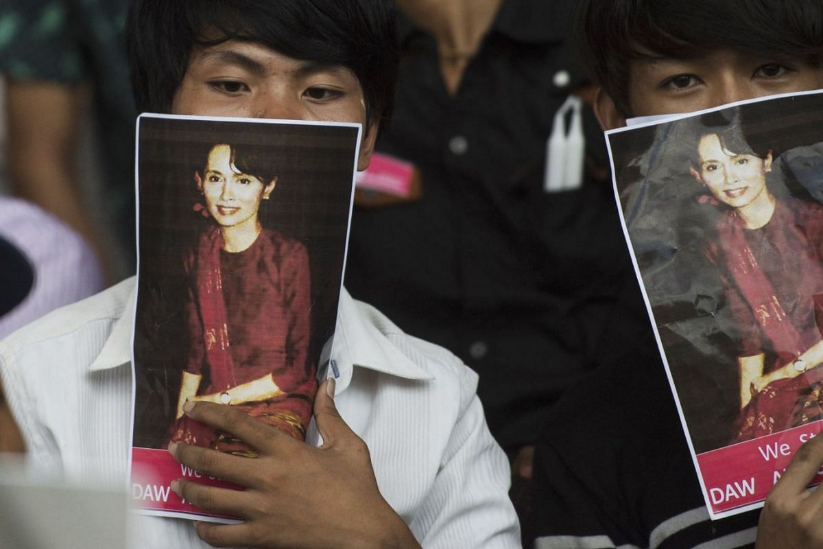 Two men attending an interfaith prayer ceremony cover their faces with portraits of Myanmar's civilian leader Aung San Suu Kyi in Yangon, Myanmar, October 10, 2017. PHOTO: AFP